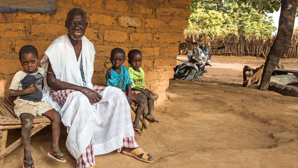 Trachoma patient Aladje sits with his grandchildren outside their home in Guinea-Bissau.