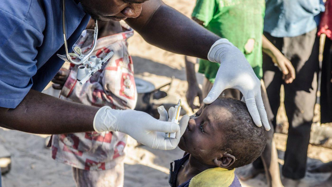 Un bambino viene visitato agli occhi da un dottore.