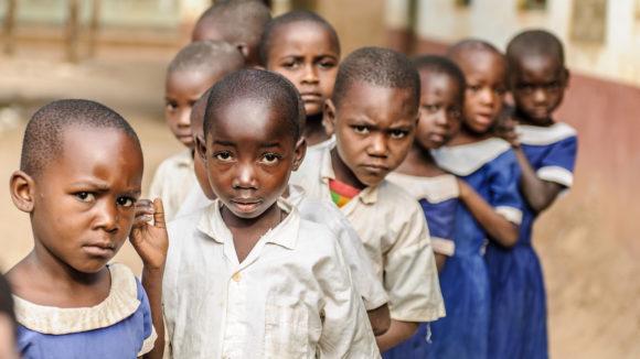 Dei bambini in fila davanti alla loro scuola in Tanzania.