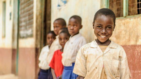 Zuhura dalla Tanzania in posa davanti alla sua scuola primaria.
