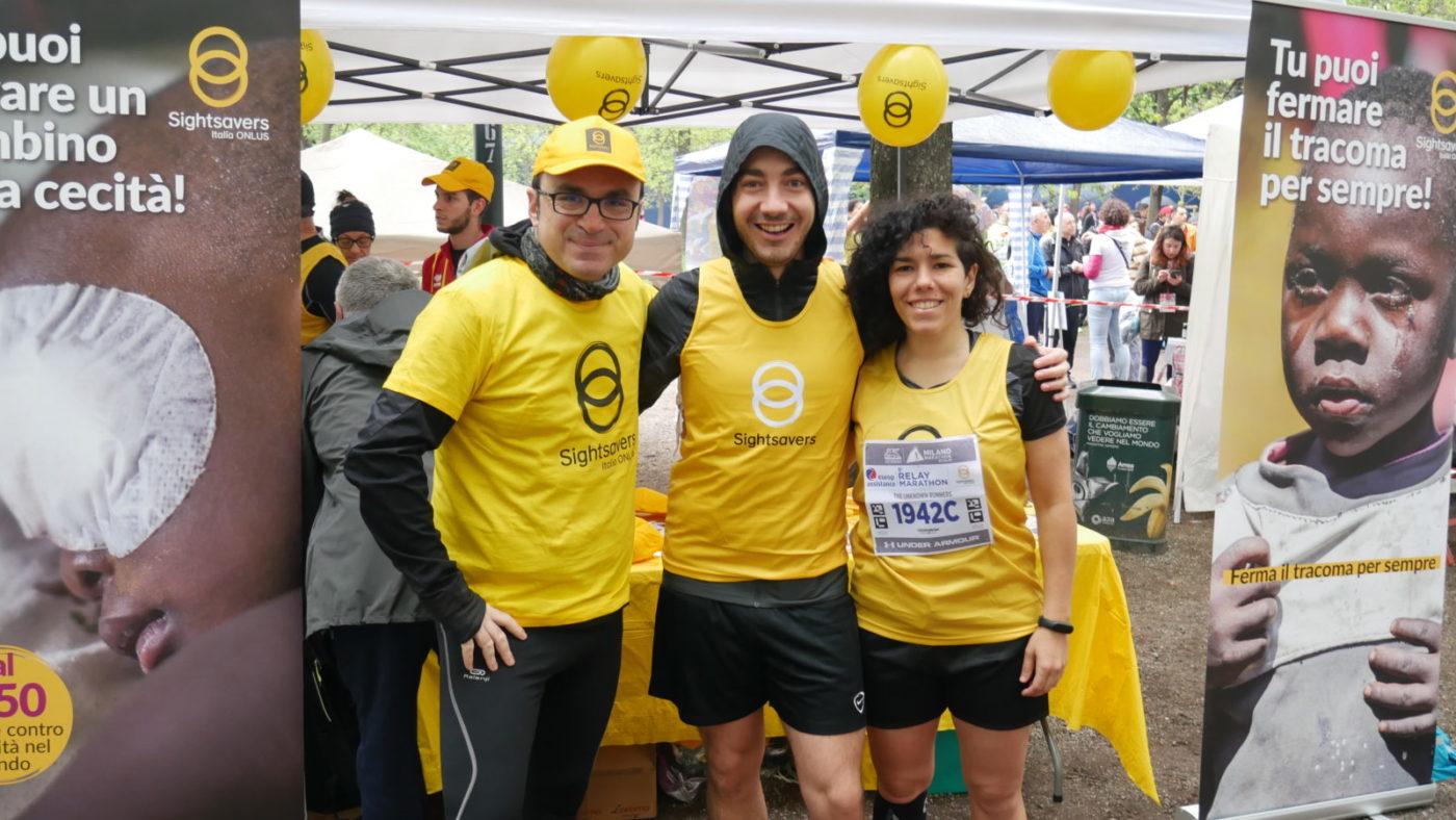 Due uomini e una donna con le pettorine di Sightsavers alla maratona