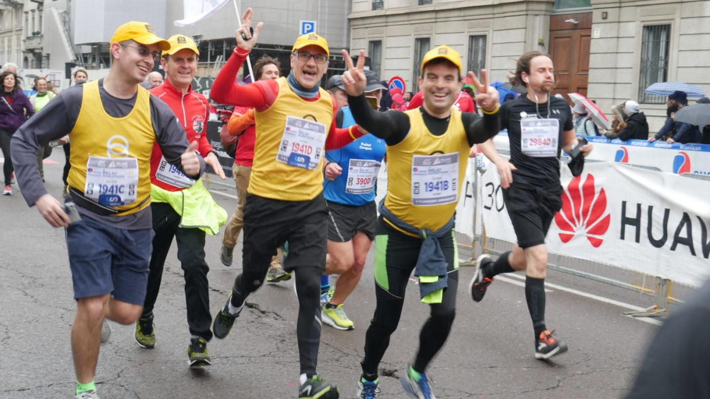 Quattro maratoneti maschi stanno correndo verso l'arrivo della maratona