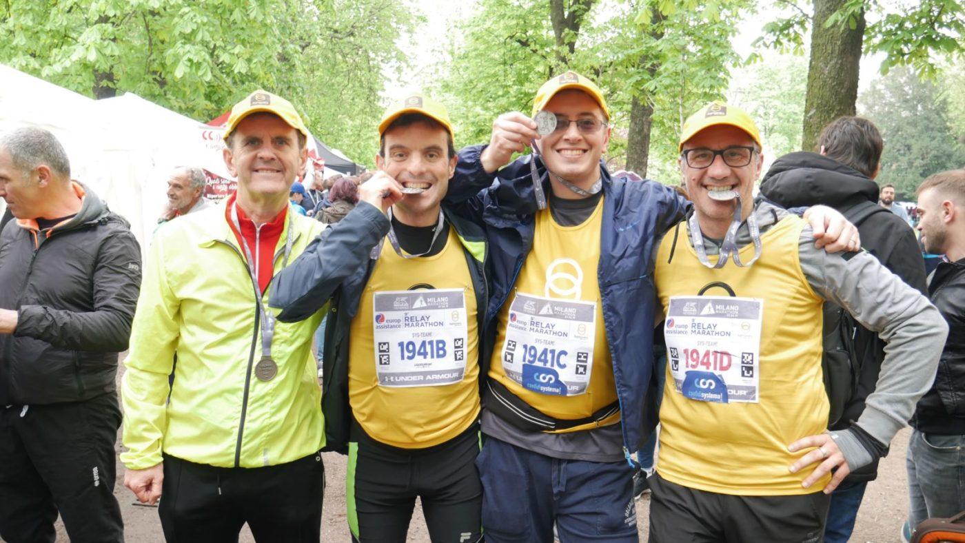 Quattro maratoneti mostrano la medaglia dopo la maratona
