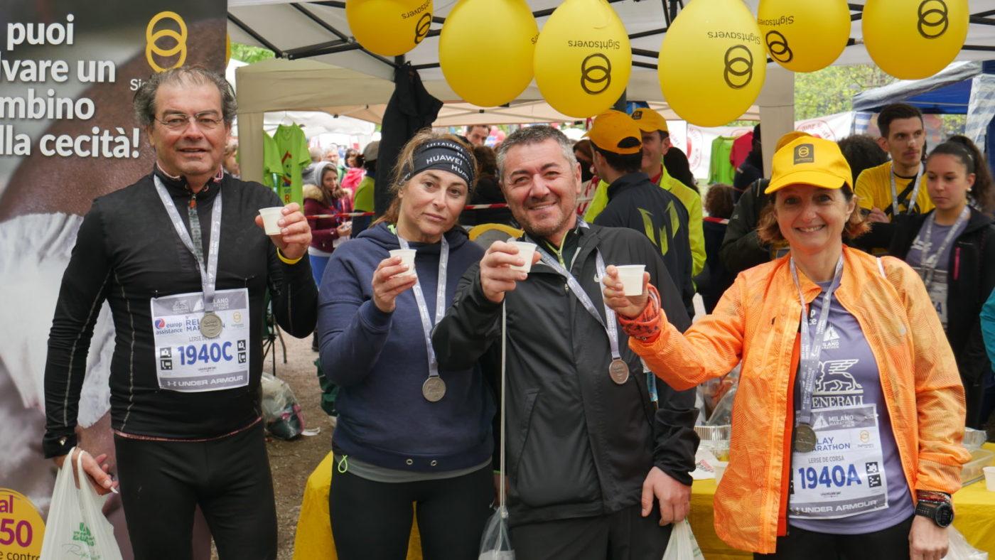 Quattro maratoneti mostrano la medaglia dopo la maratona davanti allo stand di Sightsavers