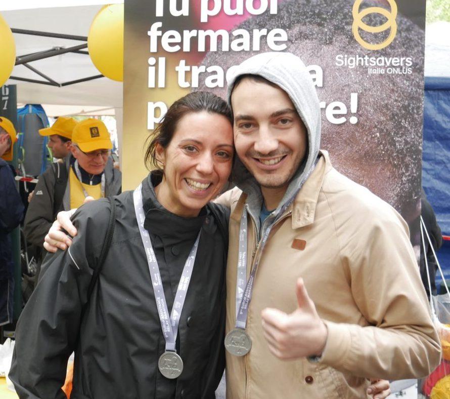 Due maratoneti maschio e femmina davanti allo stand di Sightsavers alla Milano Marathon