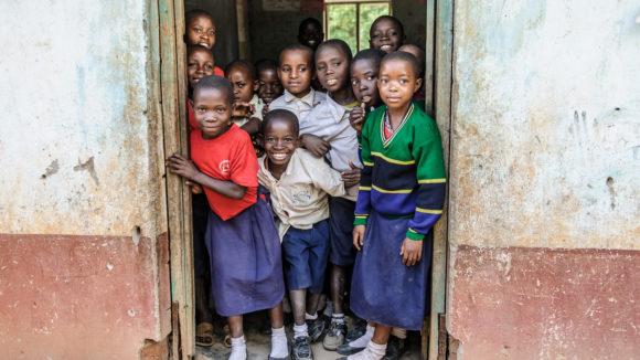 Un gruppo di bambini sulla porta sorride all'obiettivo.