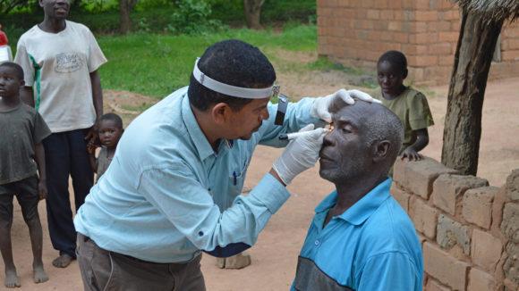 Un medico visita gli occhi di un paziente fuori casa