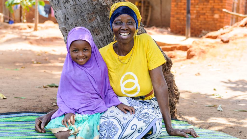 Una mamma con la sua bambina sorridono sedute per terra.