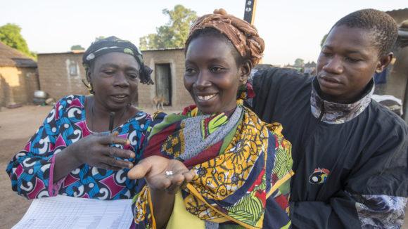 Due operatori distribuiscono la medicina a mamma Hema.