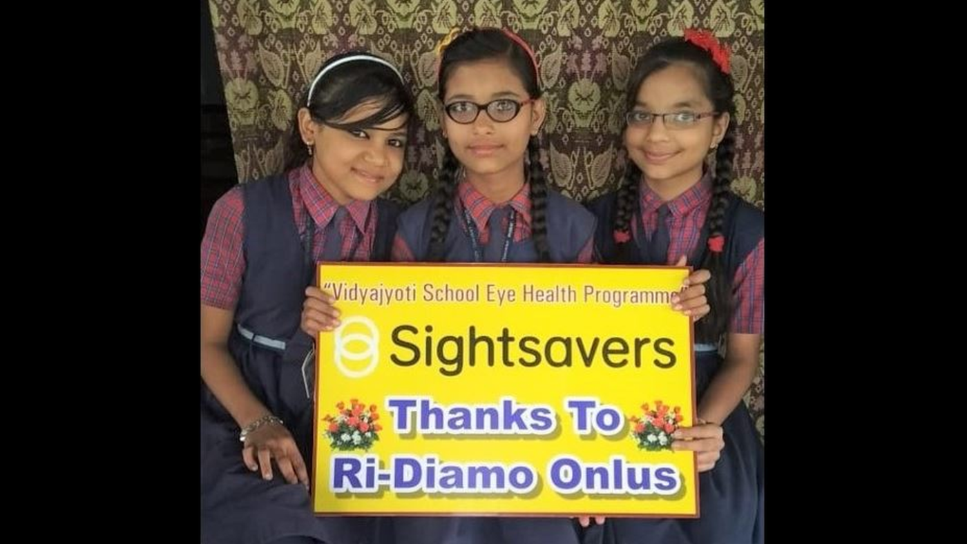 Tre ragazzine tengono in mano un cartello per ringraziare Ri-diamo.