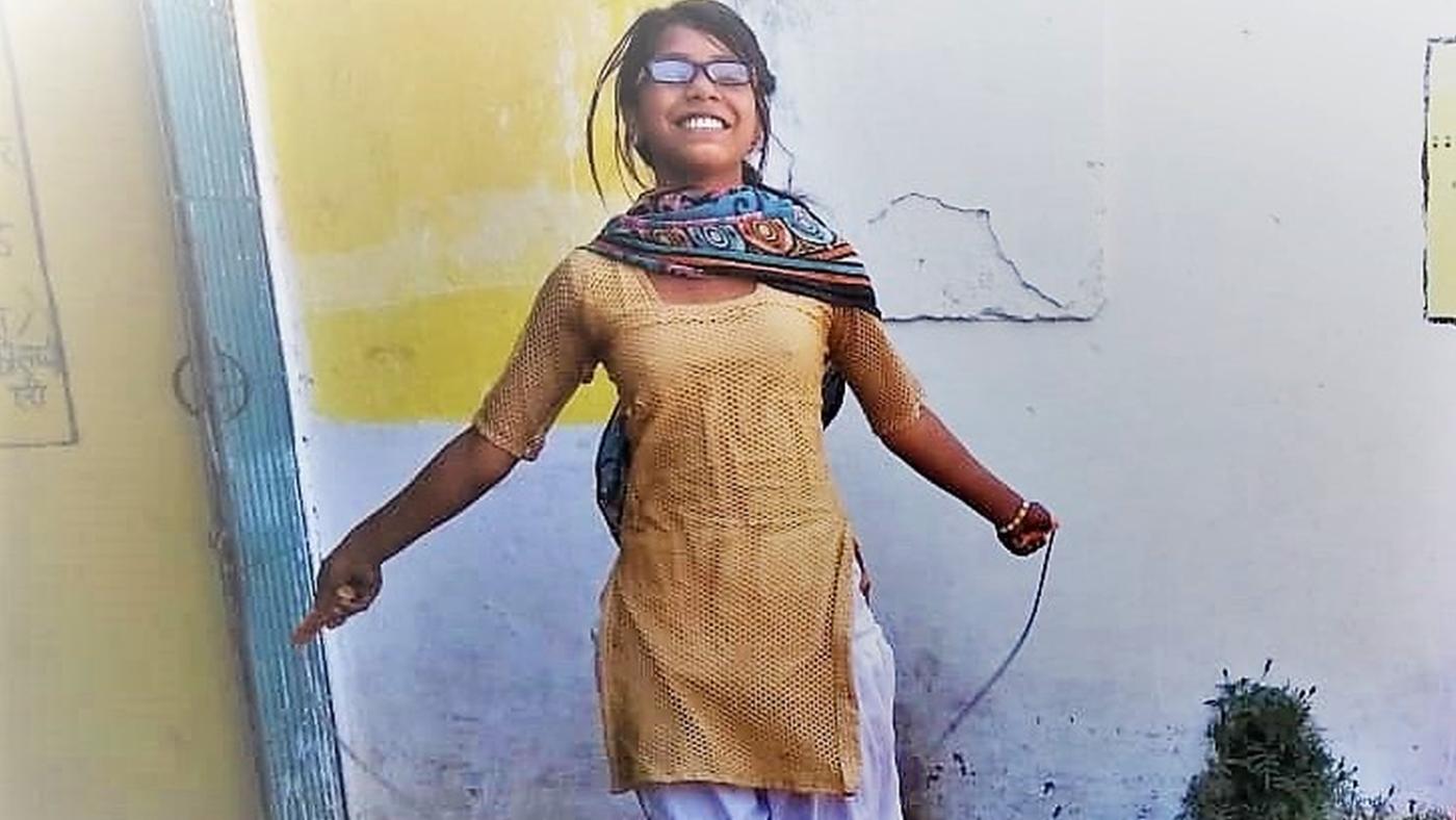 Una ragazzina con gli occhiali salta la corda.