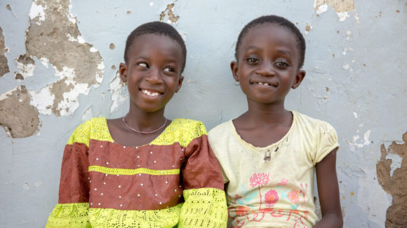 Two young girls sitting together and smiling.