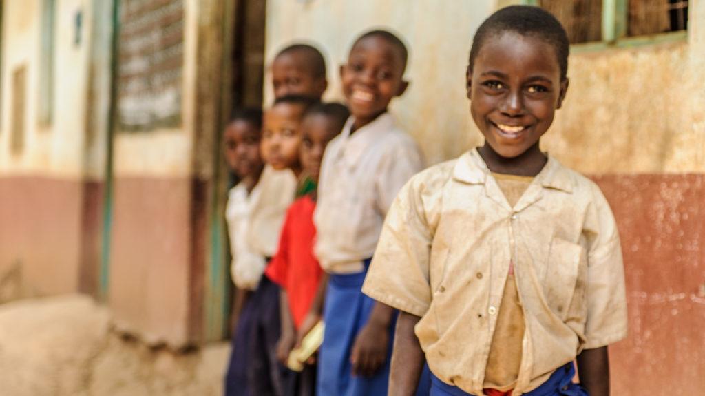 Una bmabina sorride e dietro di lei altri bambini.