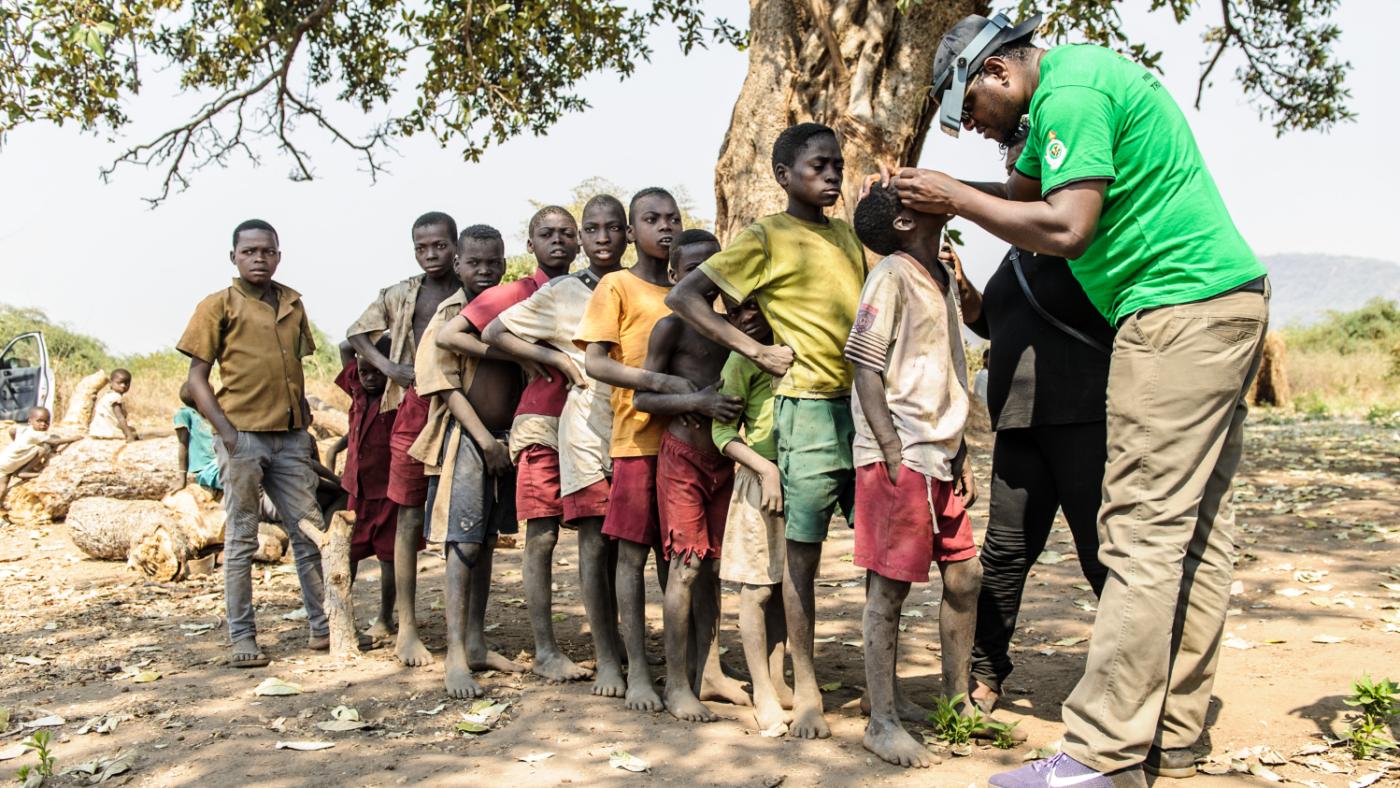 Givemore visita un gruppo di bambini in fila.
