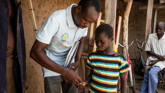 Un volontario porge ad una bambina il medicinale.