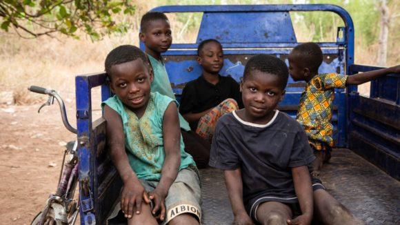 Alcuni bambini sono seduti nel retro di un pick up.