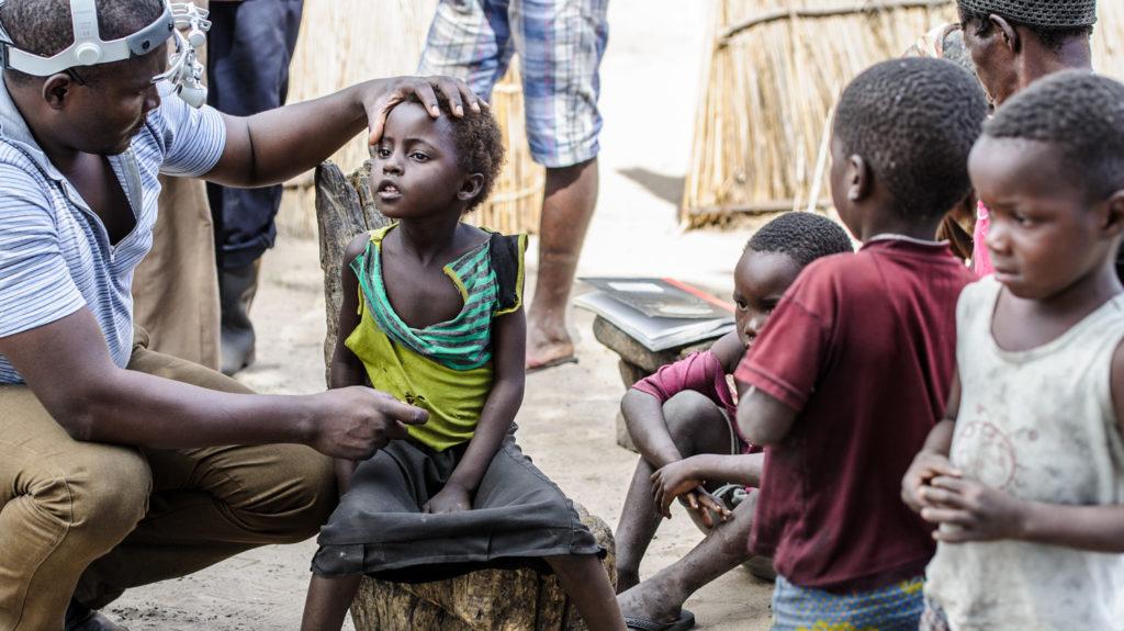 Una bambina viene visitata dal dottore e altri bambini intorno a loro.