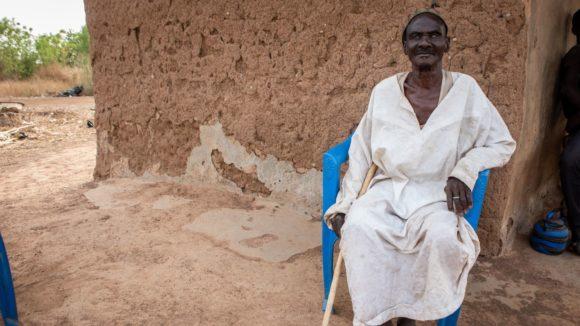 un uomo seduto difornte a casa sua.
