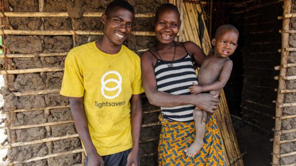 Un operatore di Sightsavers con la maglietta gialla sorride insieme ad una giovane donna che tiene il suo bambino in braccio