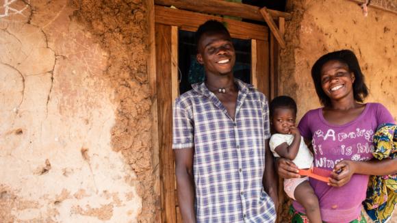 Marito e moglie e la loro figlia piccola di fronte alla loro casa di fango.