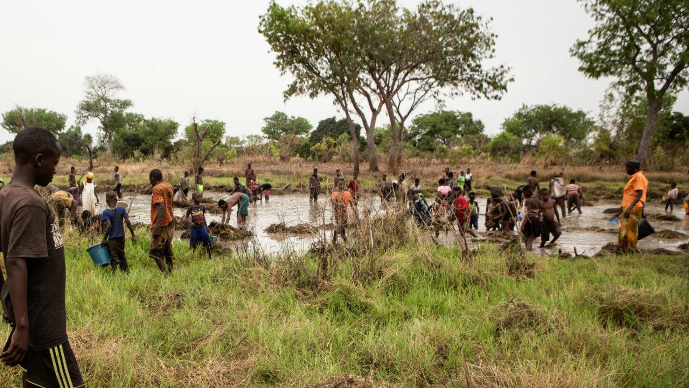 Un folto gruppo di uomini e bambini lavorano nel fiume per sistemare gli argini.