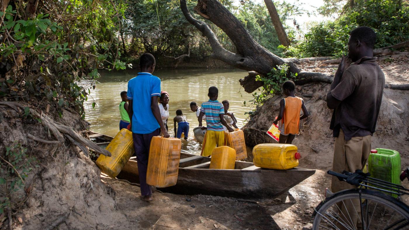 Uomini e bambini sulla riva del fiume mentre raccolgono l'acqua con delle teniche di plastica