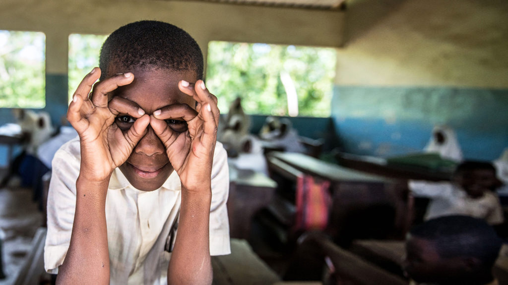 A student in Zanzibar uses his hands to imitate a pair of glasses.