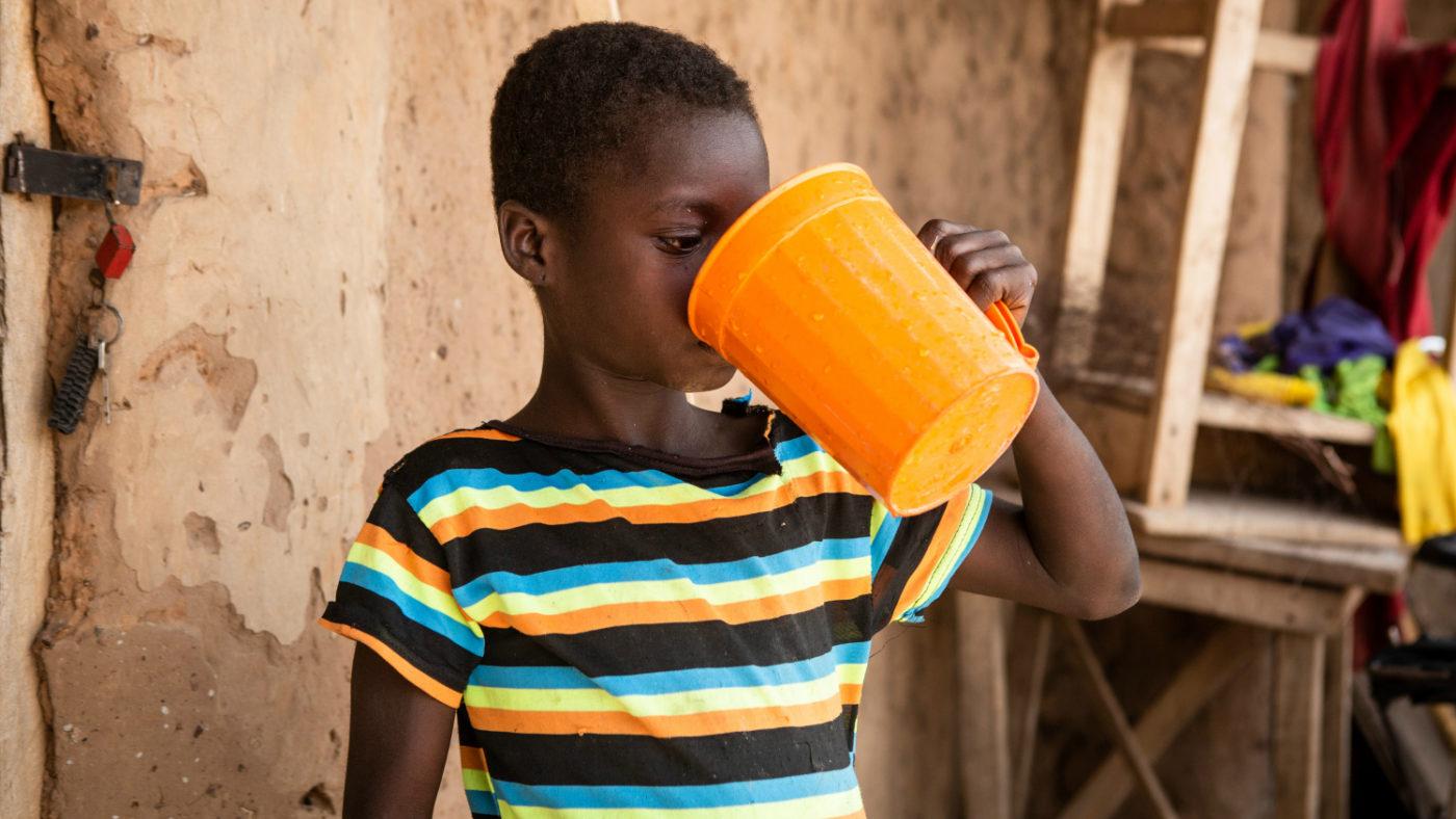 Una bambina beve da una brocca dopo aver preso la medicina.