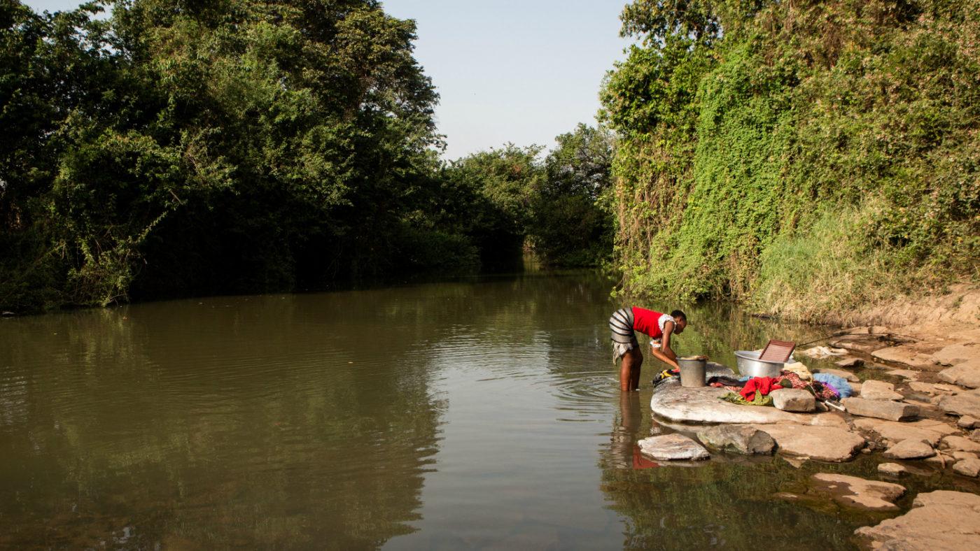 Una donna sulla riva del fiume mentre lava dei vestiti.