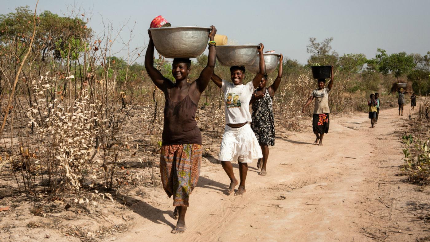 Delle donne in fila indiana, portano l'acqua con dei recipineti sopra la loro testa.