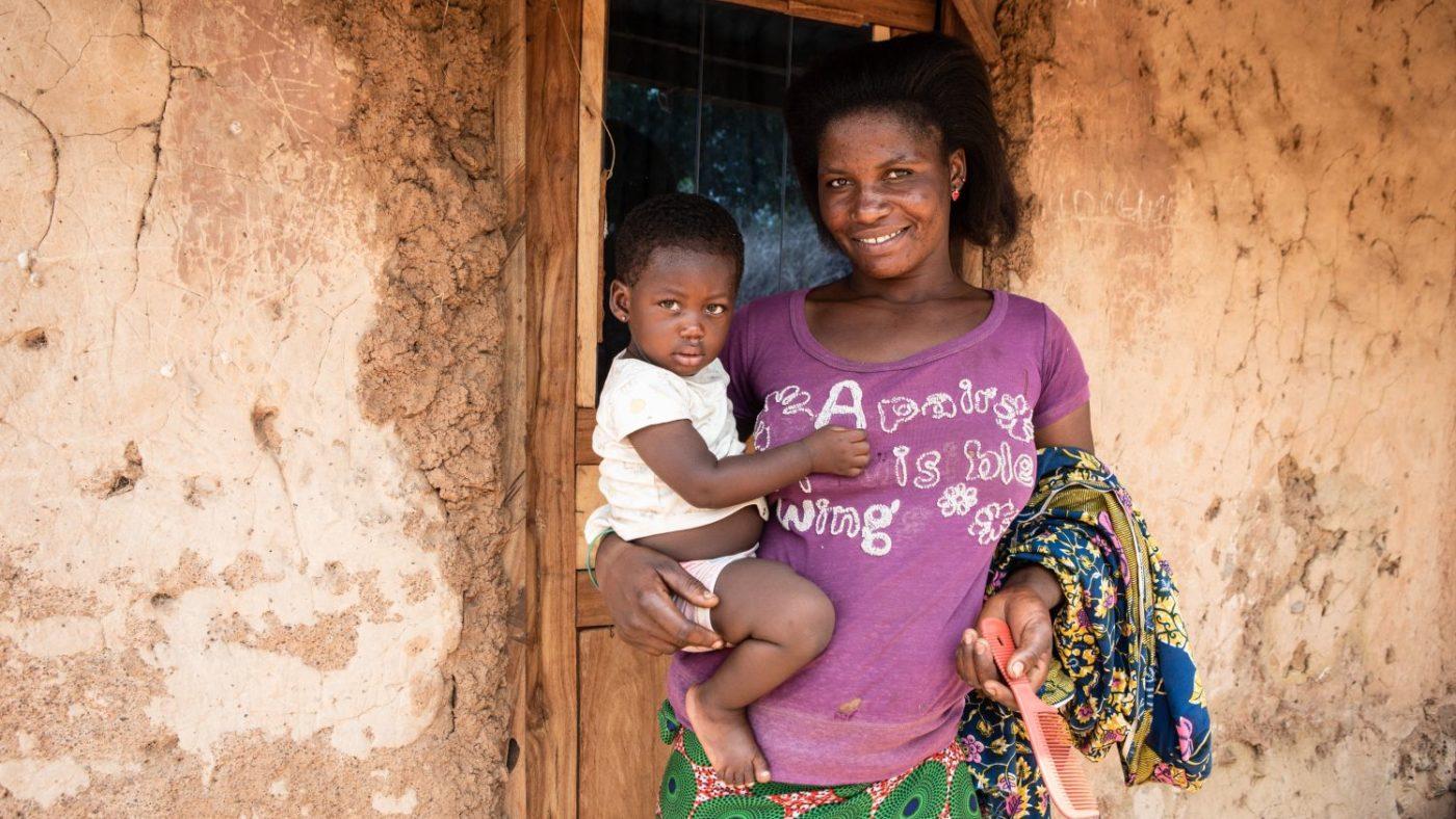 Una donna con la figlia piccola in braccio, davanti alla loro casa.