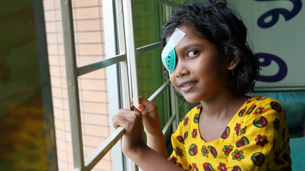 Una bambina con la benda sull occhio sorride accanto alla finestra