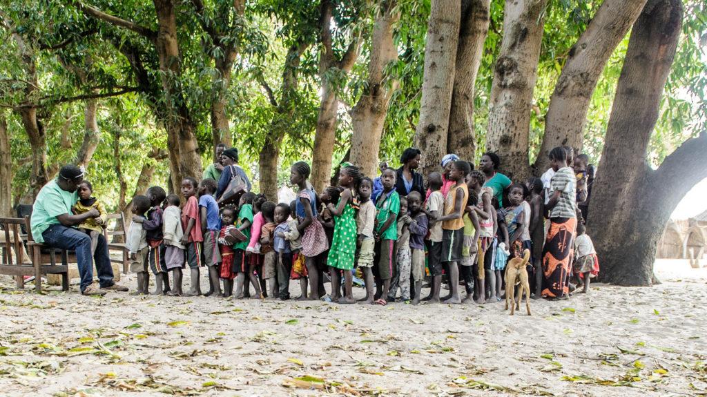 Un dottore visita i bambini in fila davanti a lui.