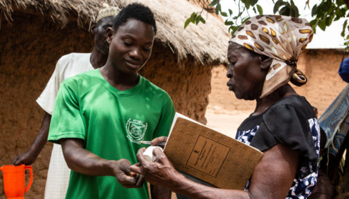 A volunteer health worker called Mary distributes a dose of Mectizan® tablets to a man in a green football shirt.