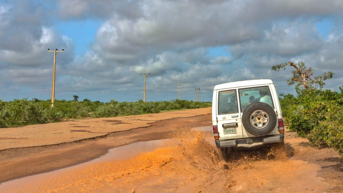 Una jeep bianca su una strada sterrata e fangosa.