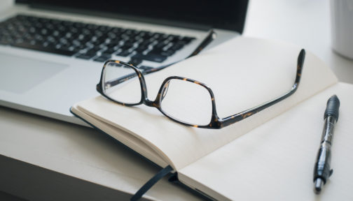 A pair of glasses, a pen and a computer on a desk.