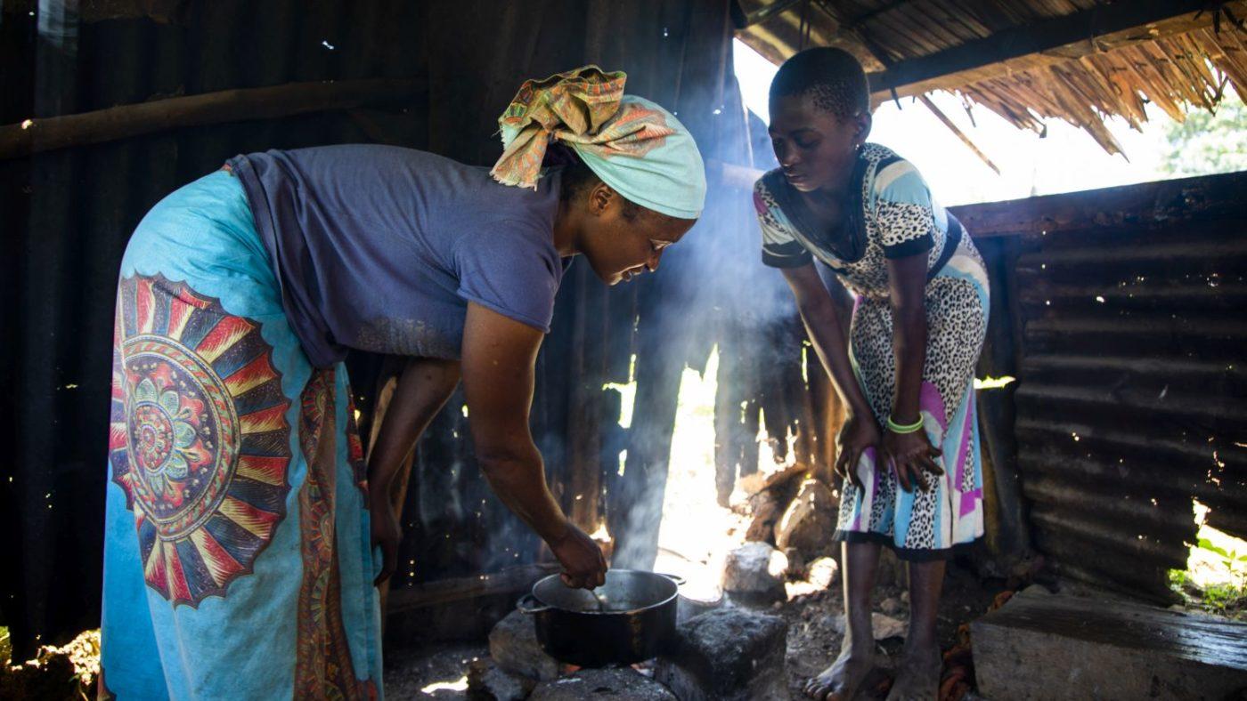 Raina cucina con la figlia nella loro capanna.