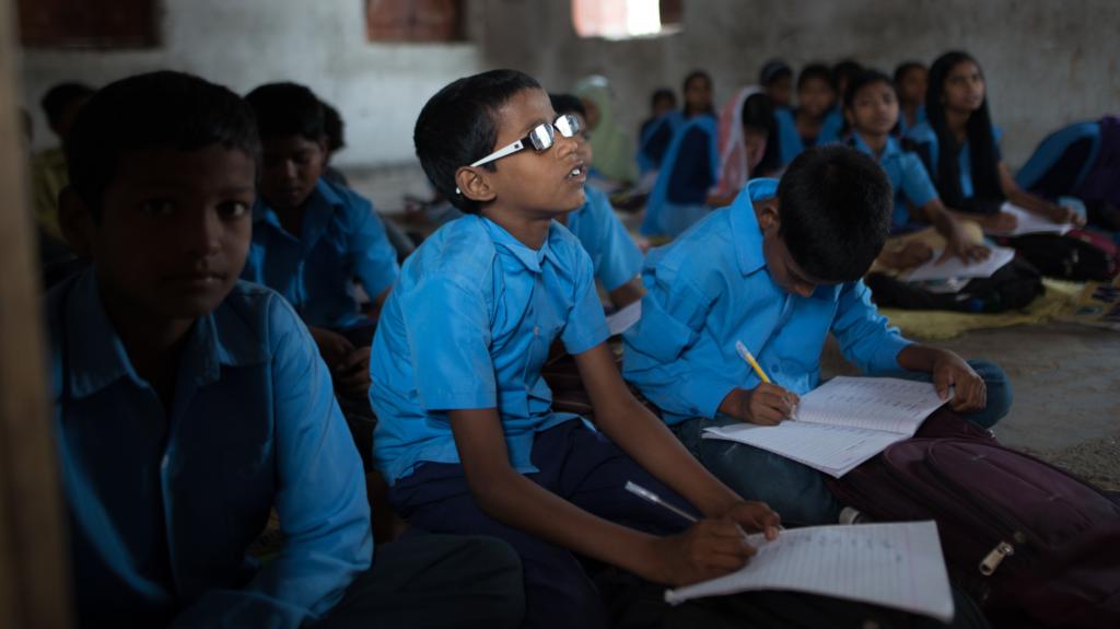 Un bimbo con gli occhiali è seduto per terra in classe insieme ad altri compagni.