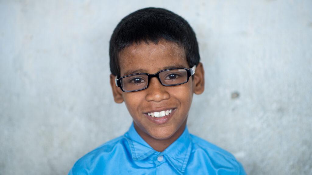 Shahid sorride con i suoi nuovi occhiali.