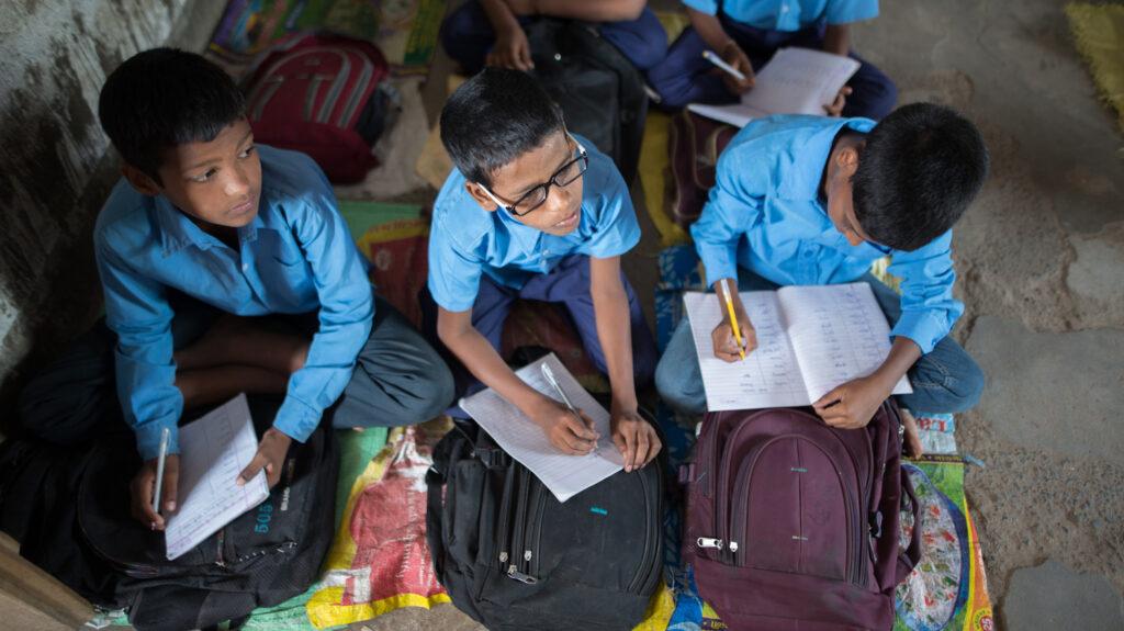 Shahid è seduto in classe con i suoi compagni.