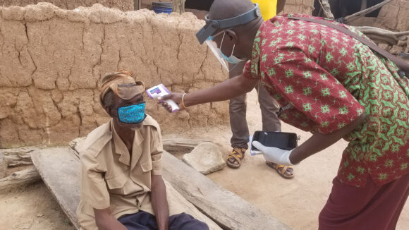 A man has his temperature checked before participating in a Tropical Data trachoma survey.