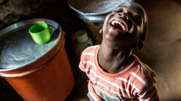 Un bambino ride felice nella sua casa.