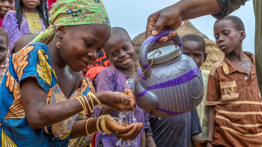 A girl in Nigeria learns how to use water to wash her face and hands.