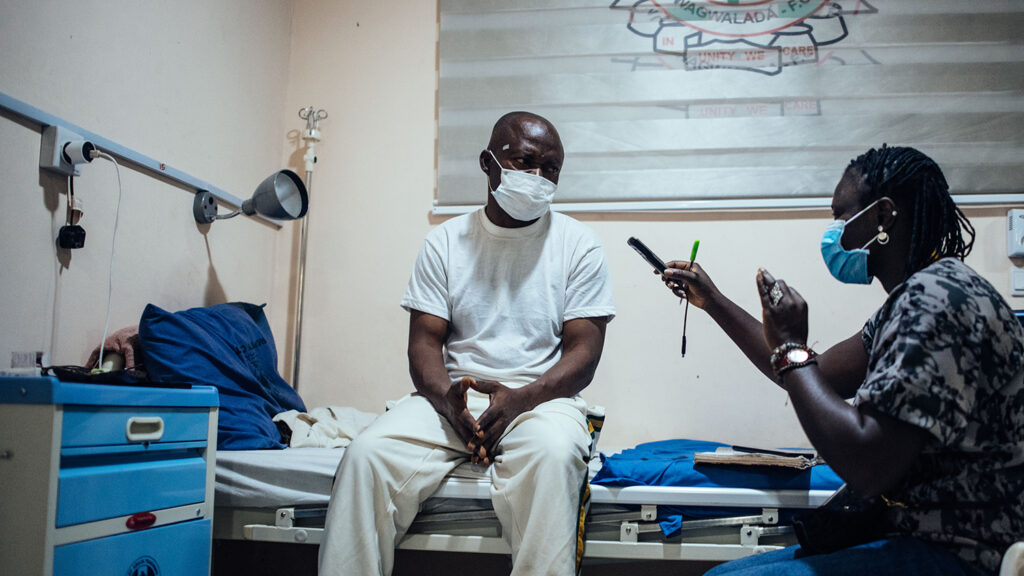 A patient is interviewed by a member of Sightsavers staff as part of a project.