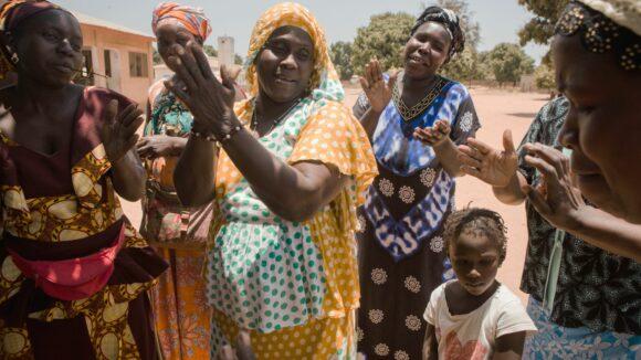 Le donne di un villaggio del Gambia applaudono e sorridono felici.