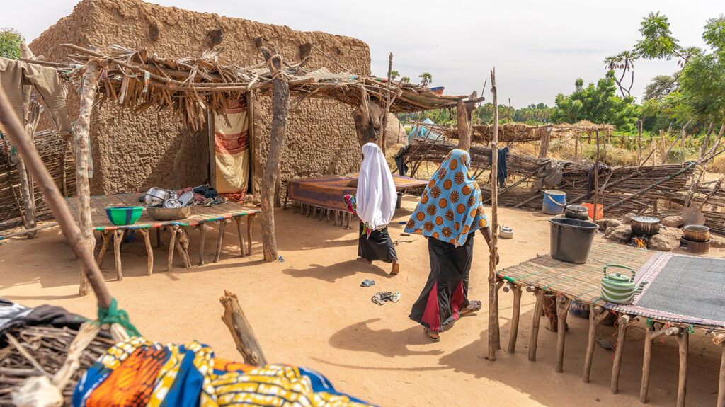 Two villagers in Niger walk among dusty coloured huts.
