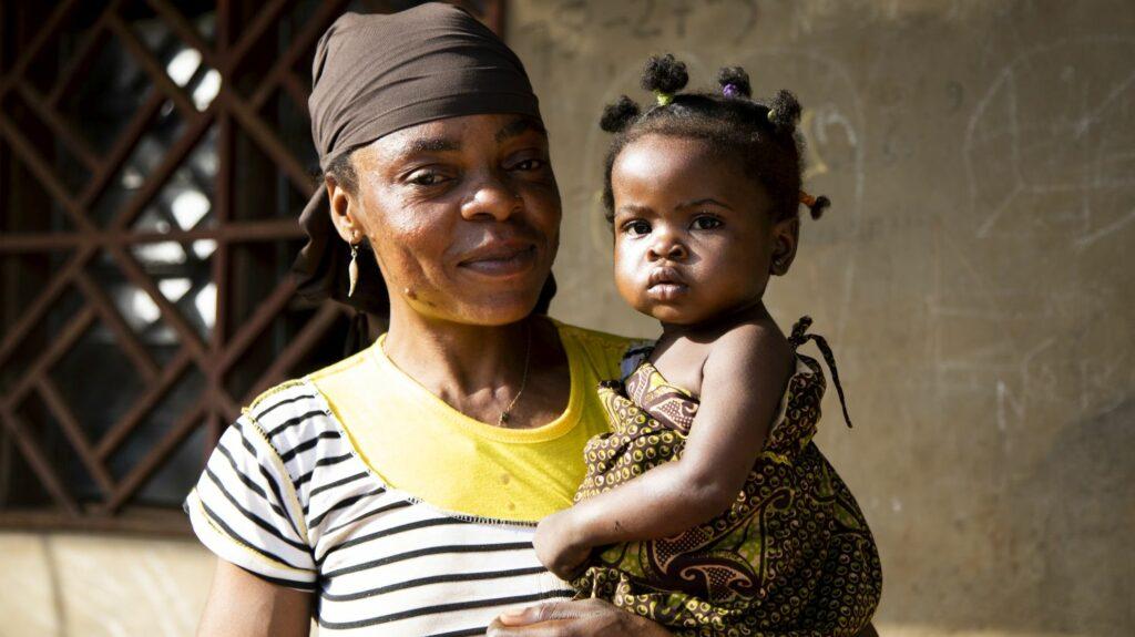 Una mamma sorride con la sua piccola in braccio.