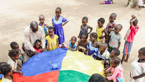 Children play with a parachute outside.