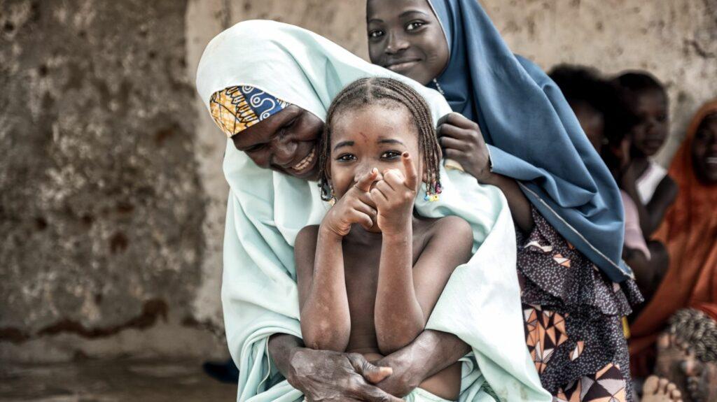Una mamma abbraccia la sua bimba che sorride.