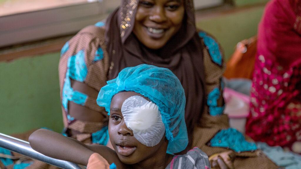 Una mamma con la sua bambina con la benda sull occhio.